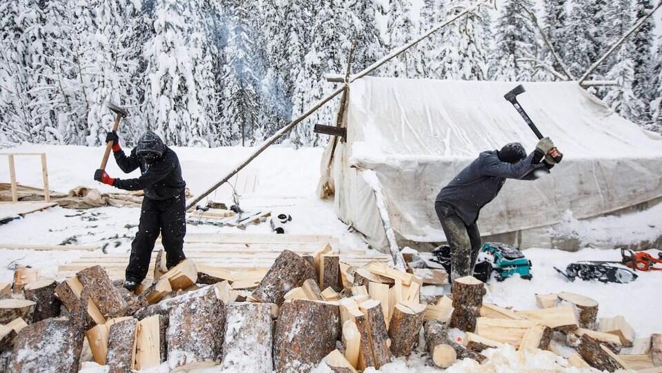 Des vidéos publiées sur les réseaux sociaux montrent des militants en train de pelleter de la neige, de couper du bois et d'élever les murs d'une cabane dans le nouveau campement.