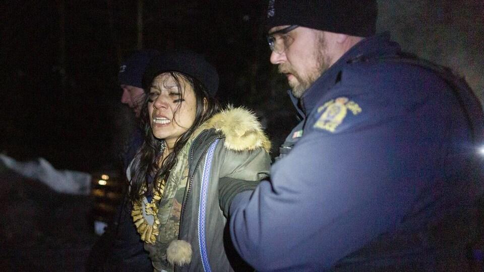 Une femme est excortée par des agents de la GRC.