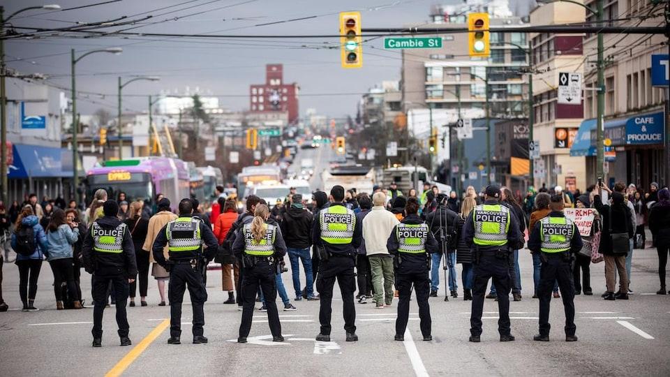 Au premier plan, sept policiers vus de dos surveillent une foule de manifestants qui se trouvent devant eux au centre d'une intersection contrôlée par des feux de circulation.