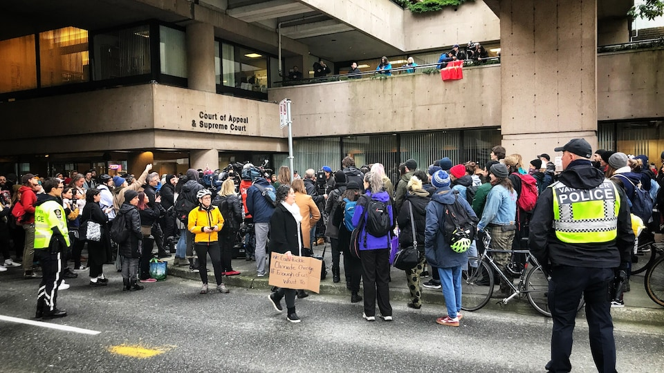 Des policiers surveillent des manifestants se sont rassemblés mercredi devant la Cour suprême de la Colombie-Britannique à Vancouver.