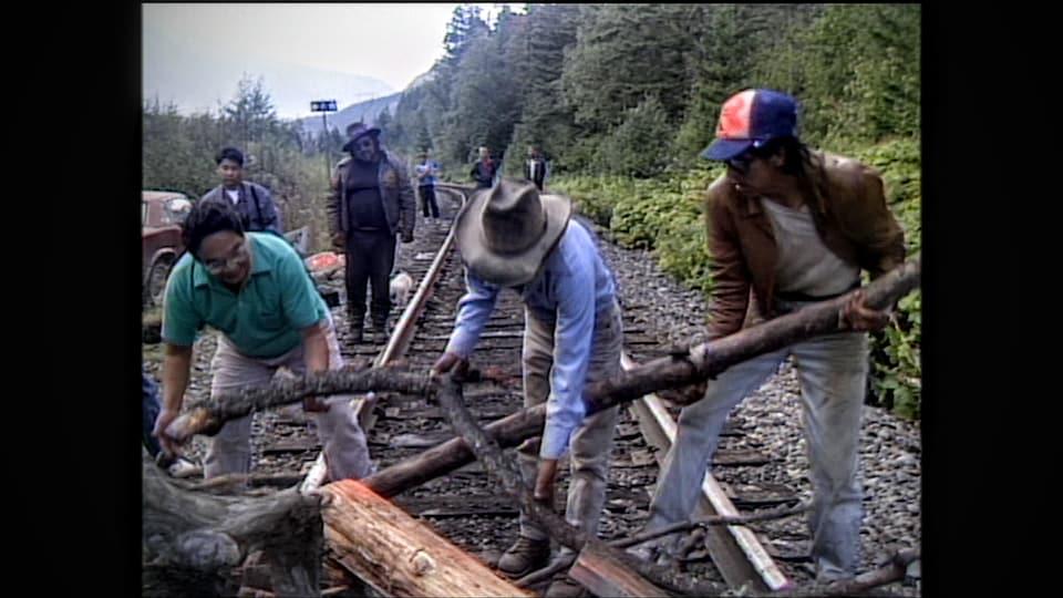Des hommes placent de grosses branches d'arbres sur une voie ferrée.
