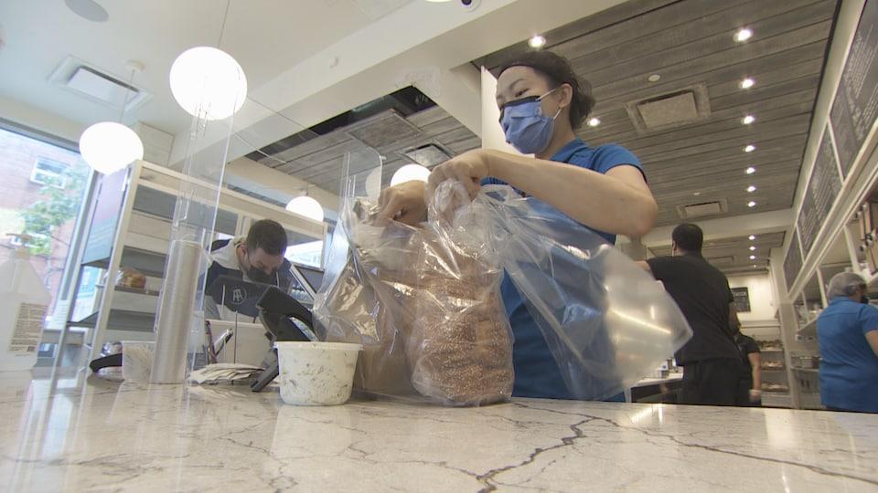 Une employée place des bagels et du pain dans un sac, sur un comptoir, avec le reste de la boulangerie en arrière-plan.