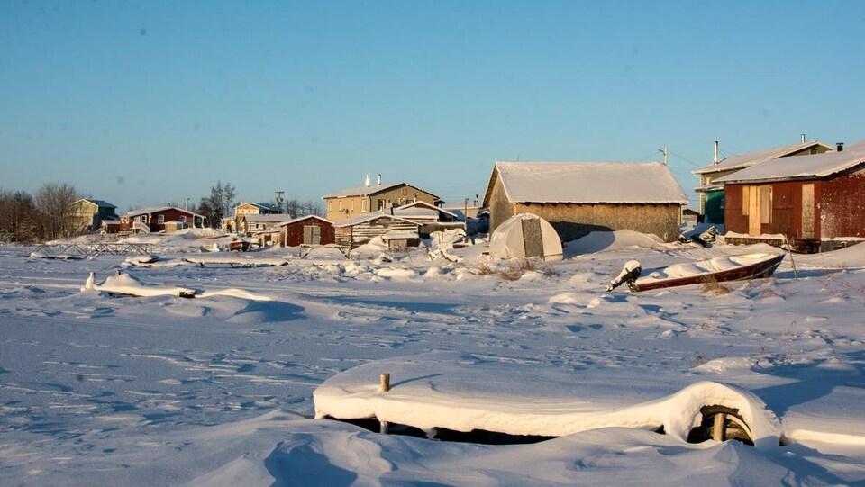 La marina de Whatì avec des quais et des bateaux recouverts de neige.