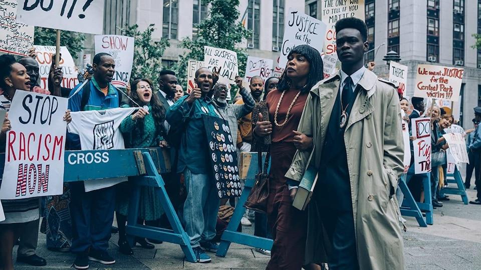 Une femme noire et un jeune homme noir avance au milieu de personnes qui manifestent.