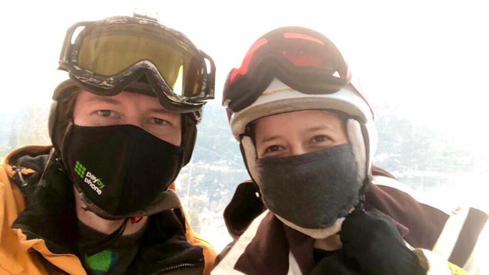 Le couple avec leur masque sur une piste de ski.