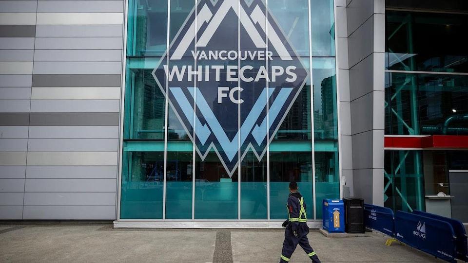 Un homme en uniforme de construction marche devant une vitre dans laquelle il y a le logo des Whitecaps de Vancouver.