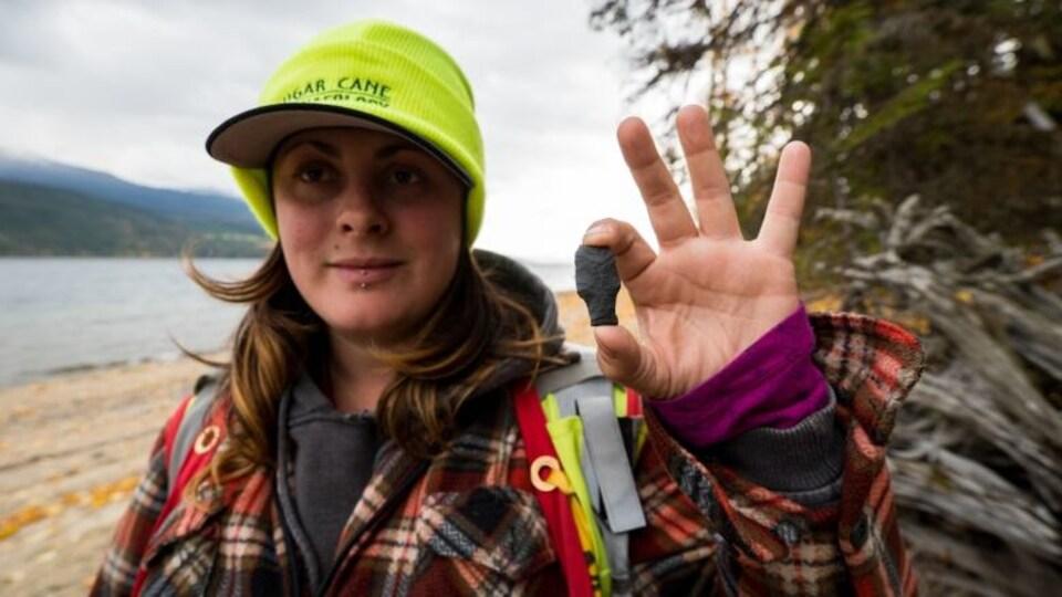 L'archéologue Whitney Spearing tient la tête de flèche.