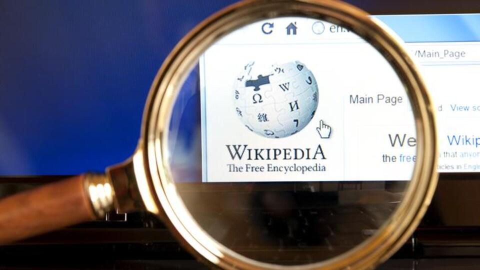 Le site Internet de Wikipédia avec une loupe grossissante.