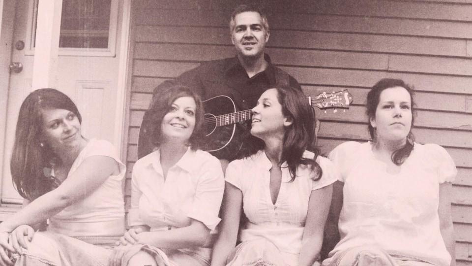 Une photo aux tons sépia d'un groupe musical composé d'un homme et quatre femmes en costume d'époque.