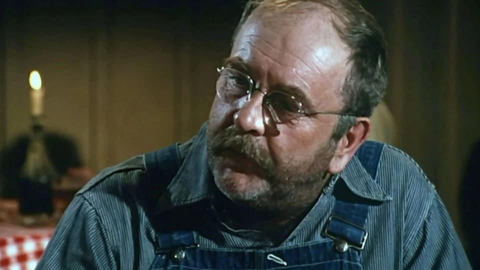Une homme avec des lunettes rondes et une salopette regarde vers la gauche.
