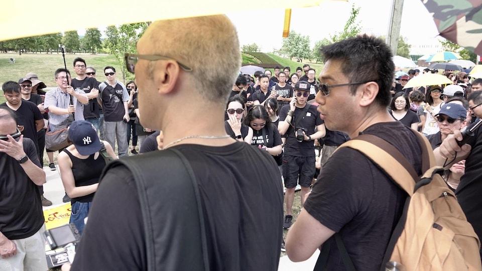 Deux manifestants de dos devant d'autres manifestants vêtus de noir.