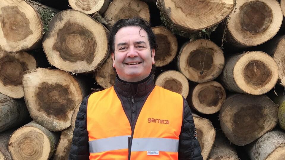 William Caine Jr. devant des troncs d'arbres coupés.