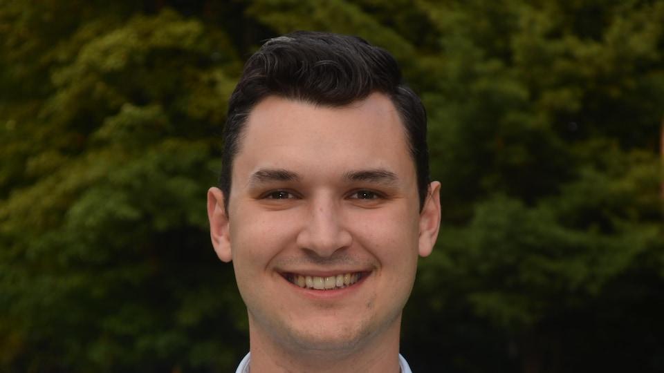 Le jeune homme dans la vingtaine sourit à la caméra devant une forêt.