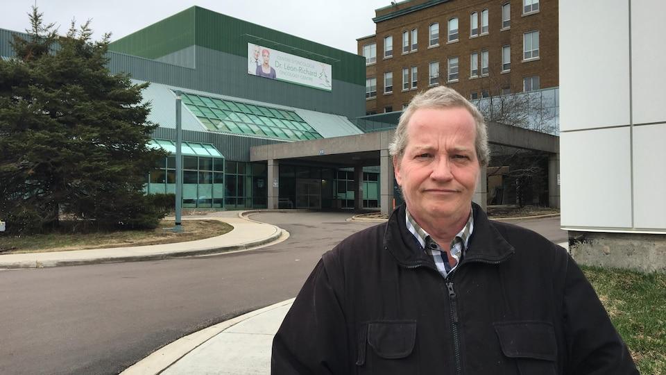 William Morissette devant le Centre d'Oncologie Léon-Richard du CHU Dumont à Moncton