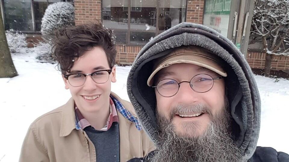 Un homme prend un selfie avec un jeune homme devant un bâtiment. On voit que c'est l'hiver derrière eux.