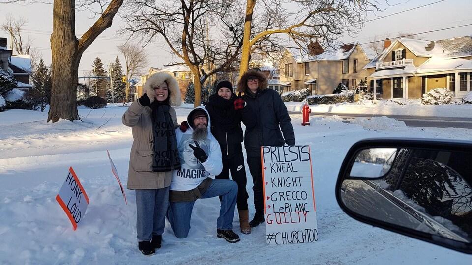 Un homme avec un genou au sol est entouré de trois femmes avec ses pancartes pour une photo de groupe.