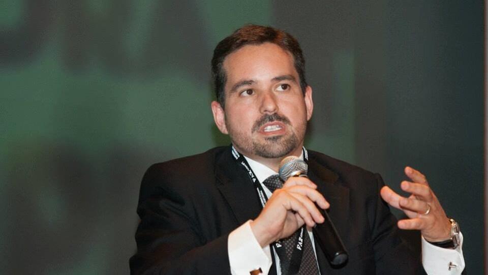 Wilson Teixeira en costume noir avec une cravate. Il parle dans un microphone.