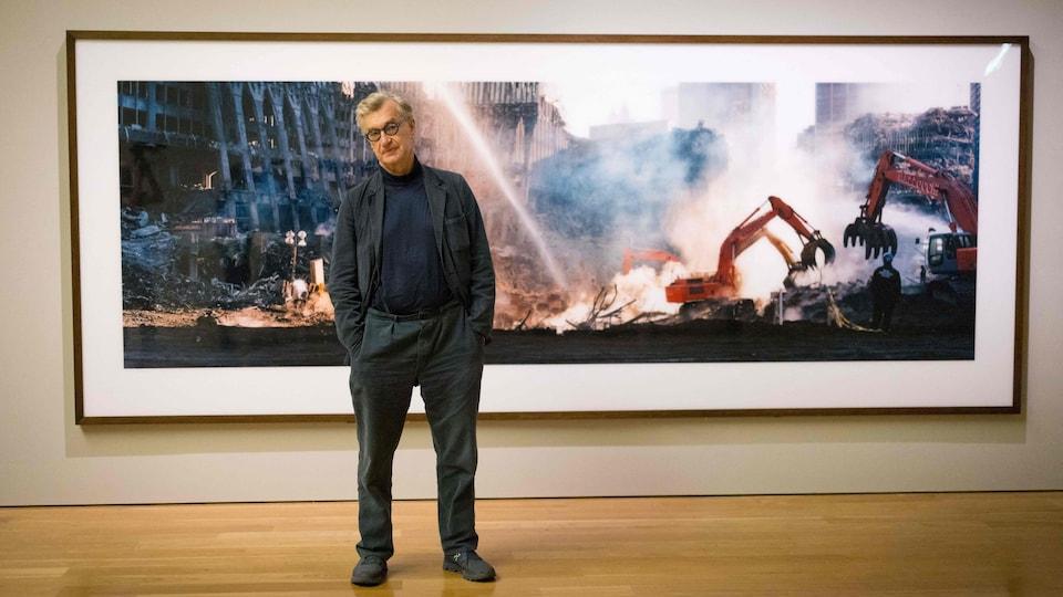 L'homme se tient devant l'une de ses photos, main dans les poches, et penche la tête comme s'il tentait d'éviter le jet d'eau qu'il y a dans la photo derrière lui.