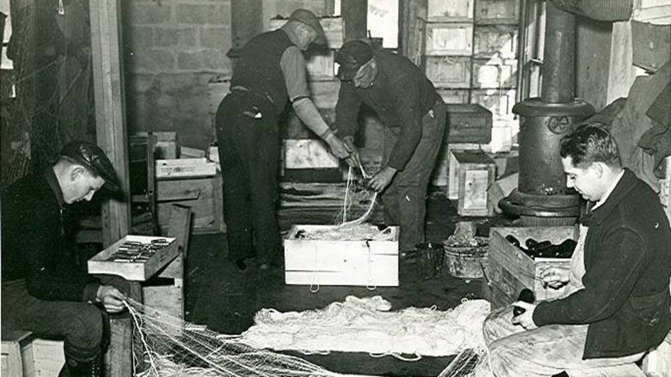 Quatre homme préparant un filet de pêche.