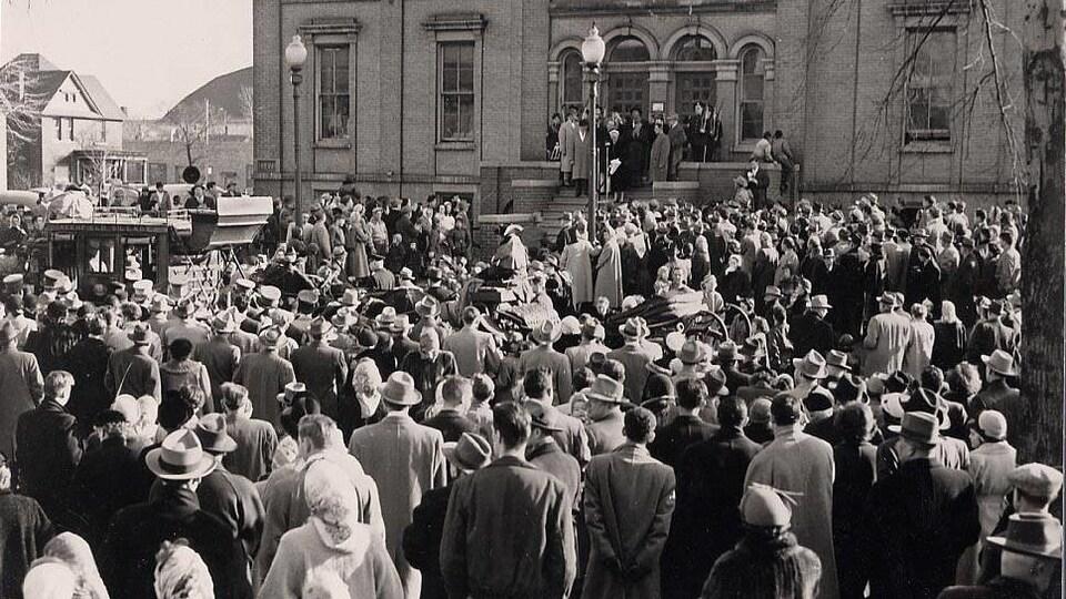 Une foule est rassemblée devant un bâtiment.