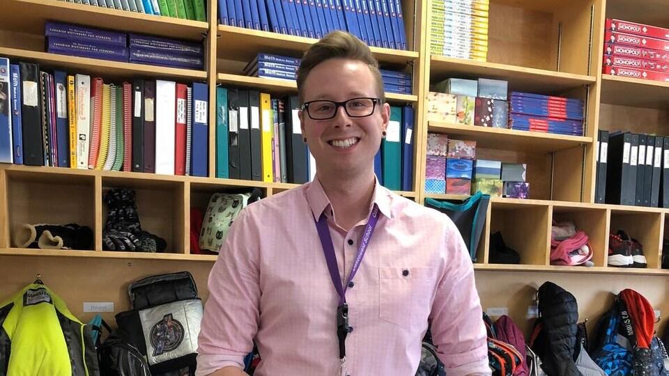 Damon Joiner, debout devant les casiers de sa classe, sourit à la caméra.
