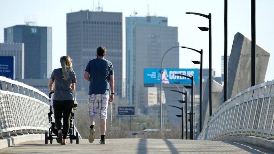 Un couple vu de dos promène une poussette sur un pont pour piétons, et les édifices du centre-ville de Winnipeg apparaissent en arrière-plan de la photo.