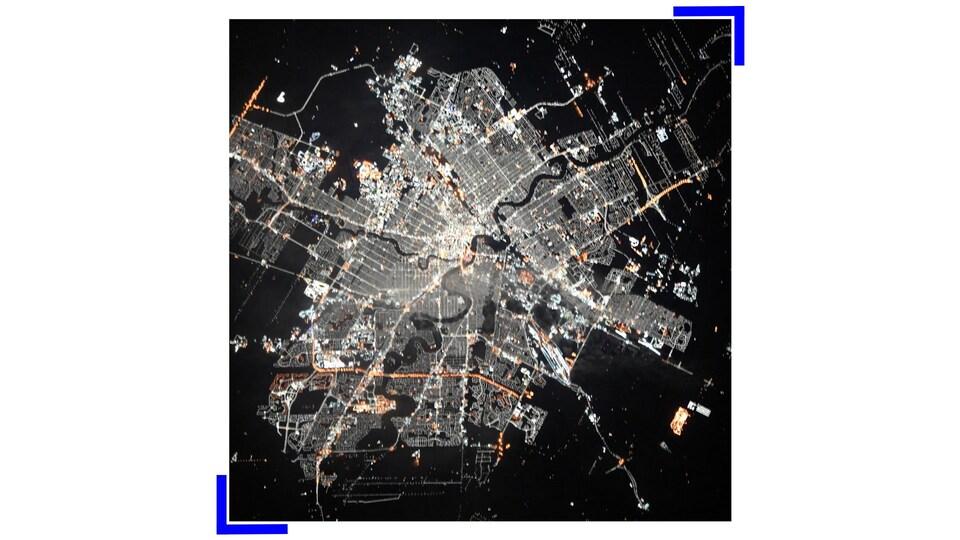 Photo aérienne de Winnipeg prise de nuit depuis la Station spatiale internationale et montrant une ville aux rues très illuminées.