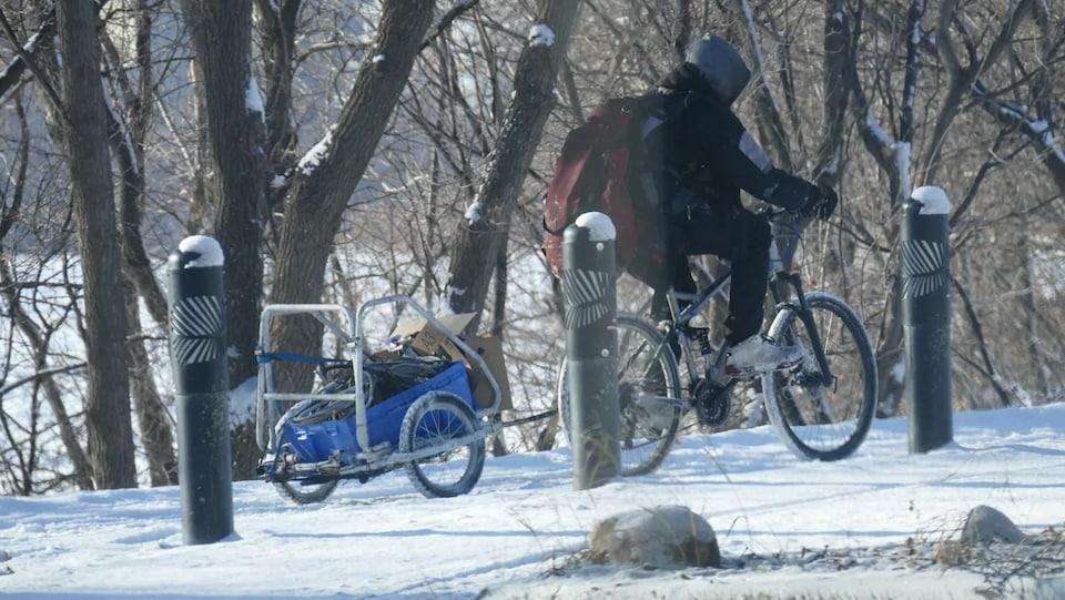 Une personne à vélo traînant un chariot plein de câbles au milieu d'un parc enneigé.