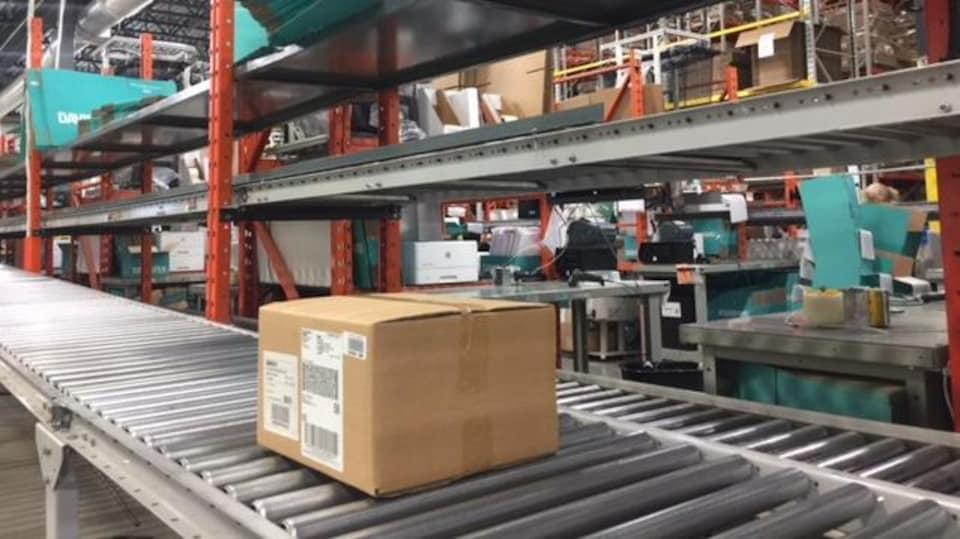 Une boîte brune circule sur un convoyeur.  On y voit également plusieurs boîtes pliées et empilées.