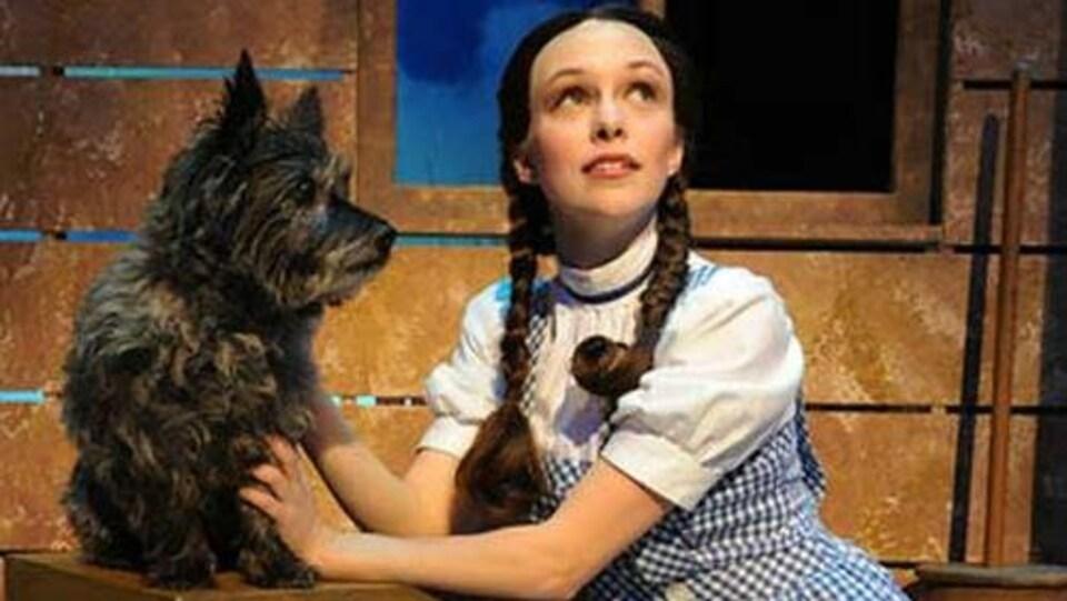 Une jeune fille sur une scène avec un chien.