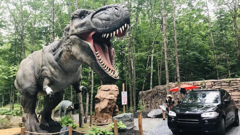 Une voiture passe devant la sculpture d'un dinosaure.