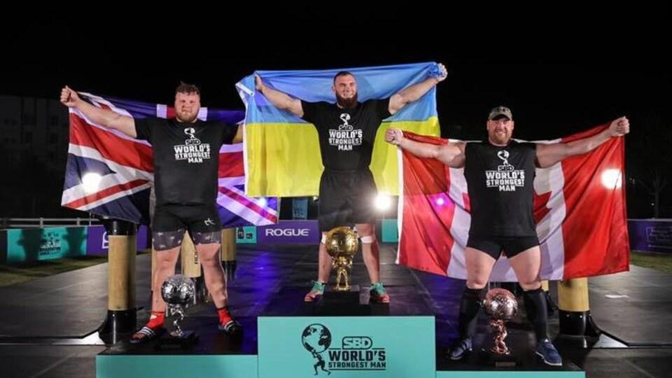 Trois hommes posent sur un podium.