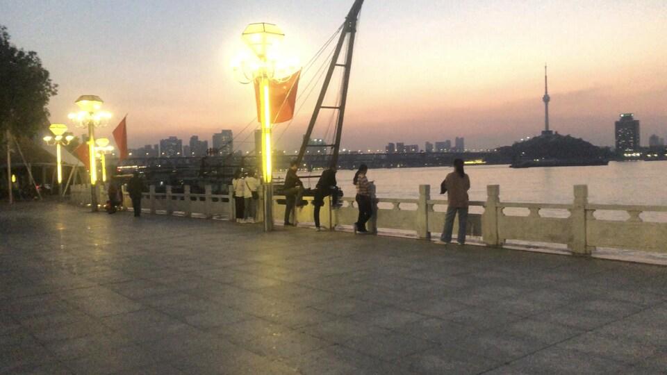 Des gens discutent sur le bord d'un cours d'eau à Wuhan.