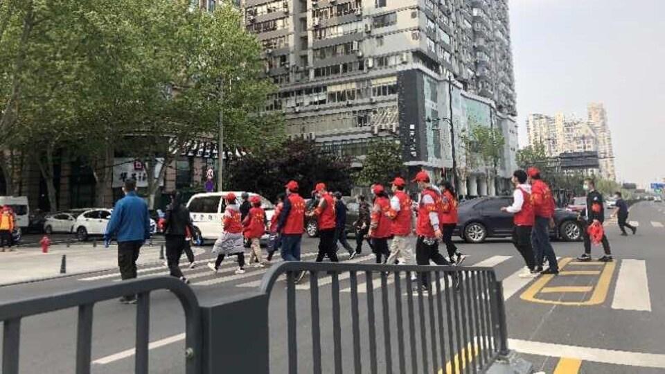 Des travailleurs bénévoles contrôlent la température de la population dans les rues.