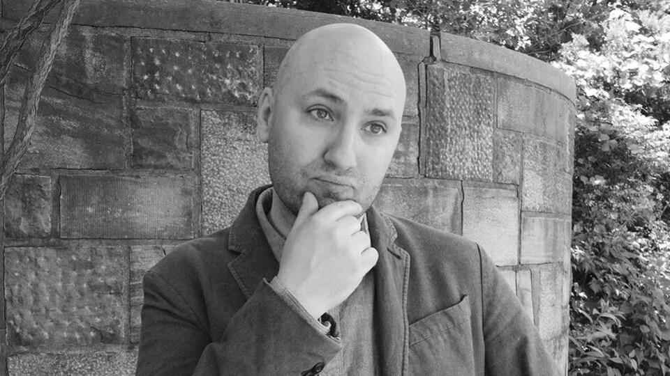 L'homme, chauve, se tient le menton. La photo est en noir et blanc.