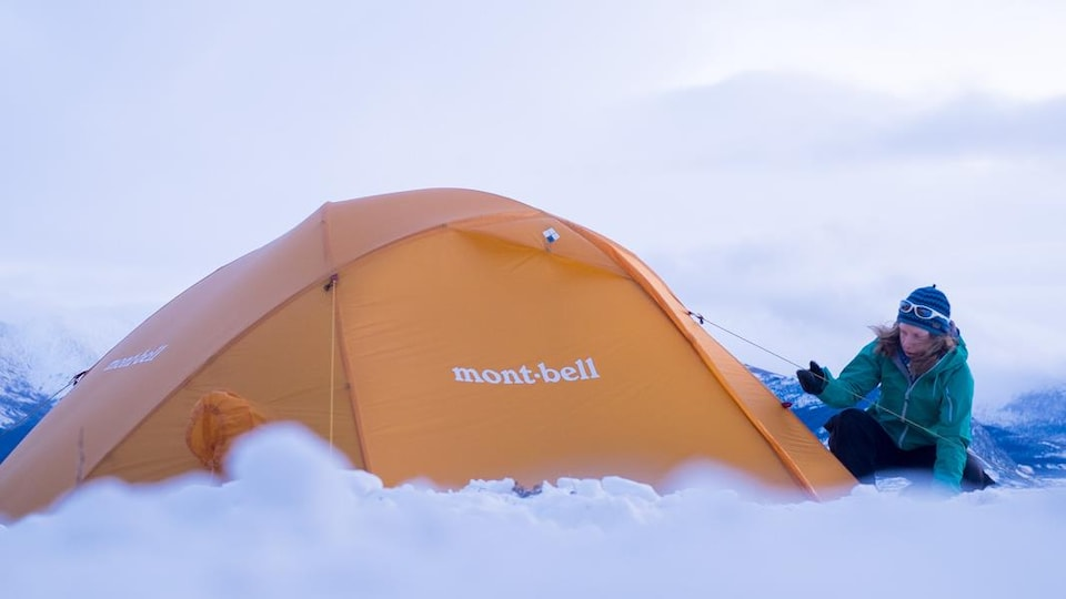 Céline Pasche près de sa tente, en hiver, dans une région montagneuse.