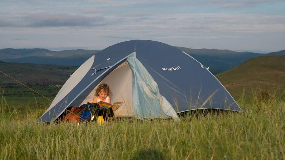 Une des filles du couple Pasche devant une tente, un livre à la main.