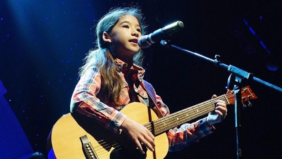jeune fille jouant de la guitare sur scène