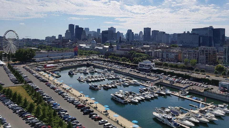 Vue panoramique du bassin de l'Horloge et du Yacht Club de Montréal, avec le centre-ville de Montréal en arrière-plan.