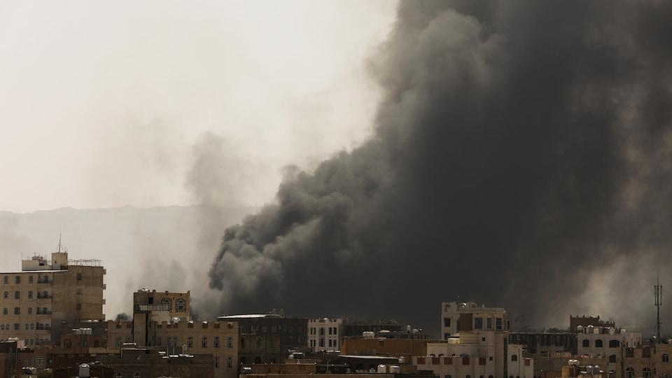 De la fumée et de la poussière s'élèvent près de bâtiments à Sanaa, au Yémen.