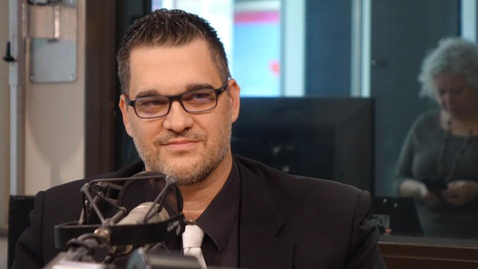 Yan Plante assis dans un studio de radio.