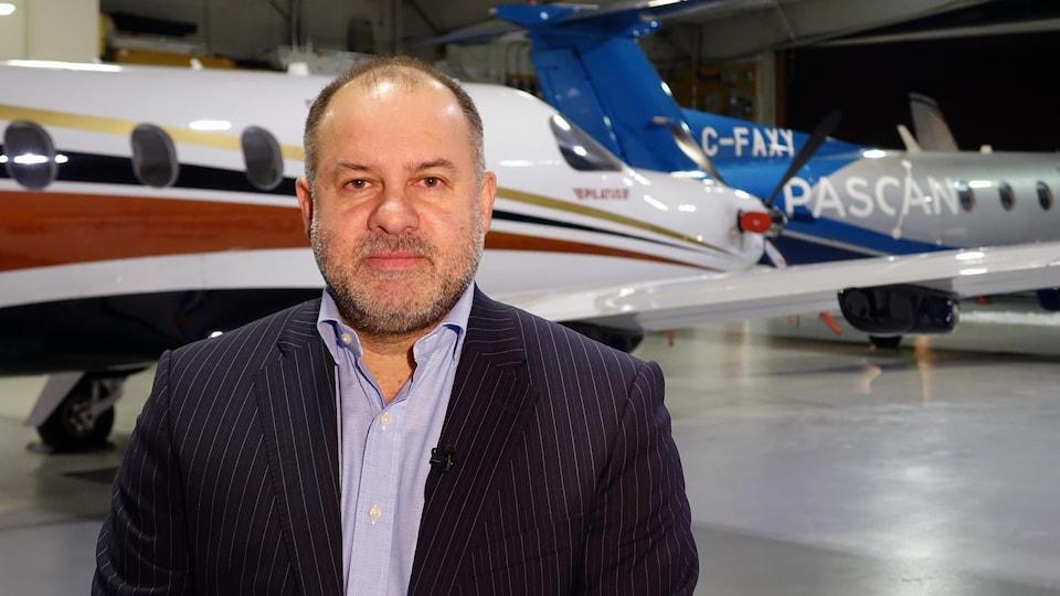 Un homme en complet se tient devant des avions dans un hangar.