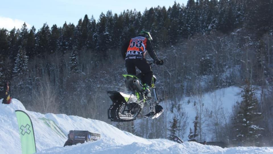 Un coureur de snow bike effectuant un saut.