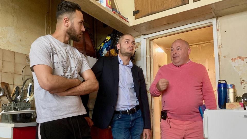 Un homme qui porte un chandail gris discute avec un homme vêtu de rose de la tête aux pieds, à droite. Un autre homme les sépare.