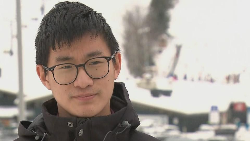 Un homme avec lunettes devant des pentes de ski.