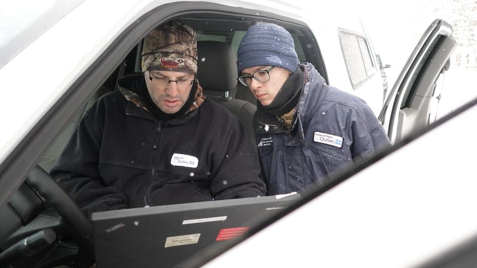 Le biologiste Yannick Bilodeau et le technicien de la faune Charles-Étienne Gagnon consultent les caméras de surveillance des sangliers sauvages.