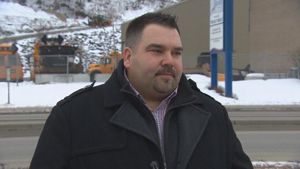 Un homme accorde une entrevue devant le service des travaux publics de la Ville de Saguenay.