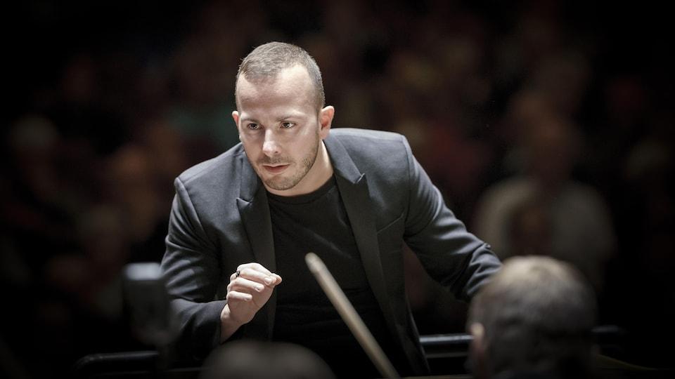 Le regard concentré, le chef d'orchestre dirige à la main son ensemble.