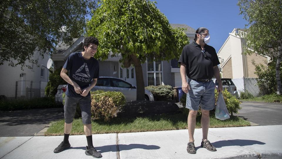 Yanny et Jacques Mignault, qui porte un masque, se tiennent à distance, sur le trottoir d'un quartier résidentiel.