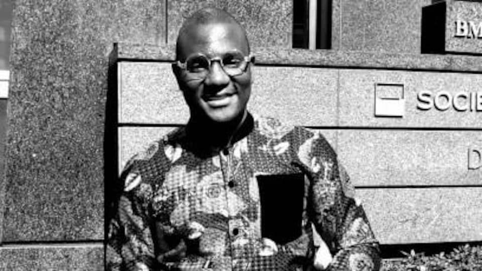 Un homme noir qui porte des lunettes et qui sourit